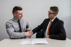 Two men shaking hands over paperwork