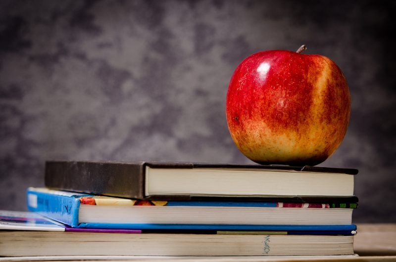 close up on an apple on books